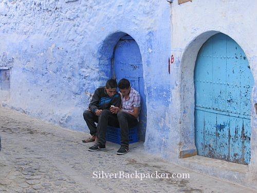 Chefchaouen teenagers sitting on blue crate texting