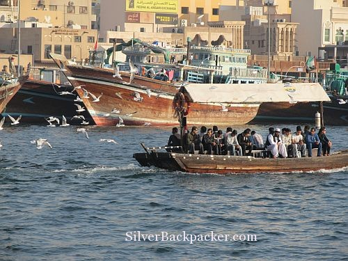 Abra passing Dhows Dubai Creek