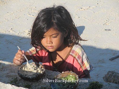 Girl playing with sand and seaweed Caluya