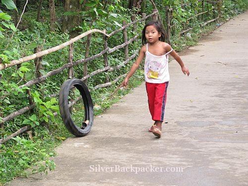 San Miguel Girl playing with tyre and stick
