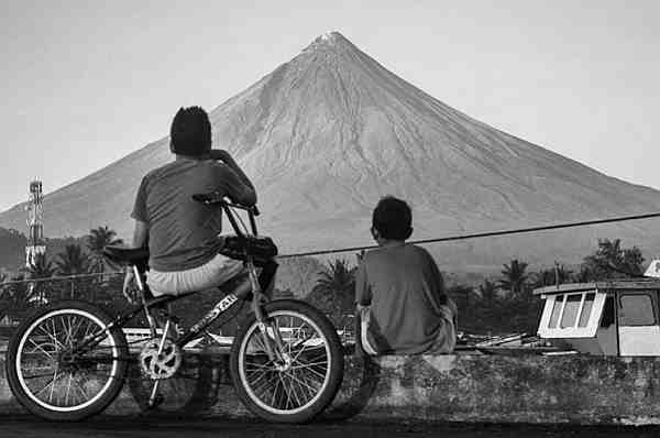 two boys on bike looking at volcano