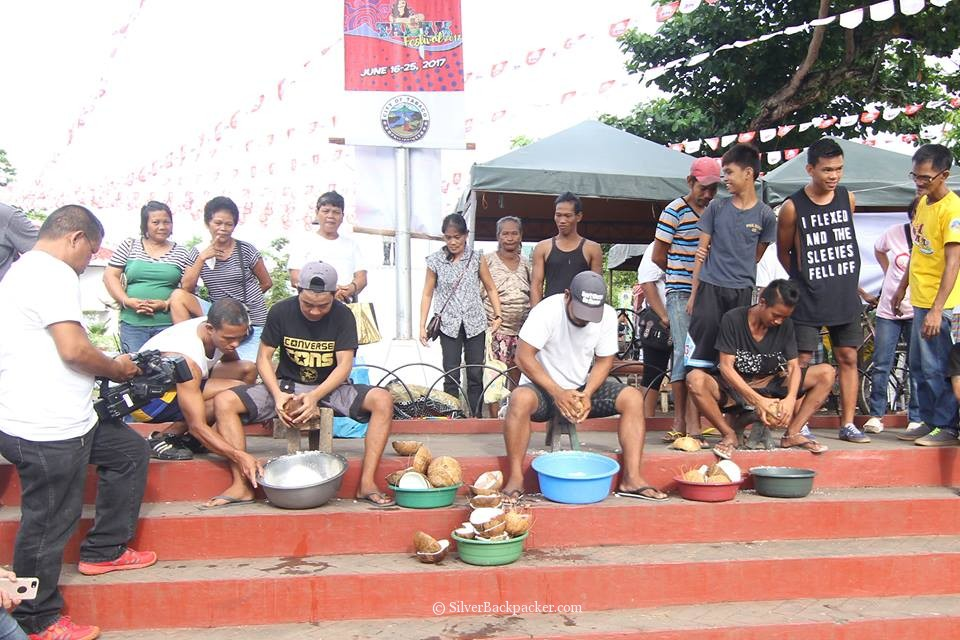 Using a kudkudan to grate the coconut meat. tabak festival