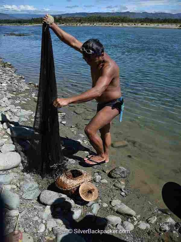 fisherman checks his net. Fishing on the Abra River